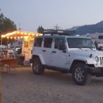 A white Jeep Wrangler parked in front of a camper set up with outdoor lights at dusk