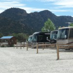 RVs in their sites with a cabin in the background