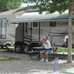A man waving in front of an RV